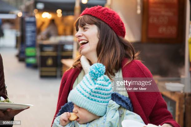 Mother carrying baby in sling is laughing, walking in street market.