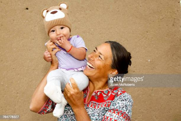 mother carrying baby son on shoulder - indian baby stock photos and pictures