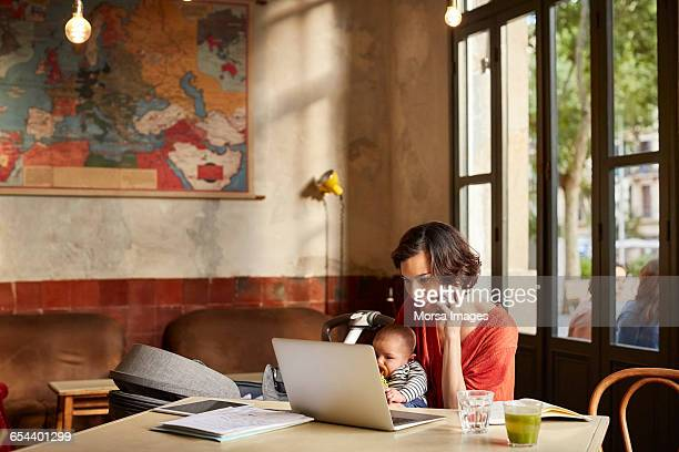 Mother carrying baby using technologies at table
