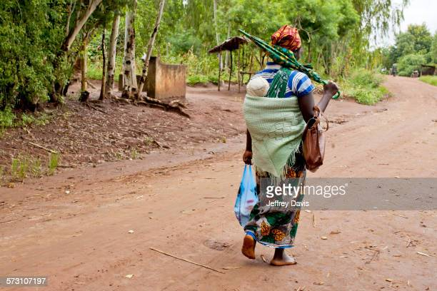 mother carrying baby with traditional wrap on dirt road - malawi stock pictures, royalty-free photos & images