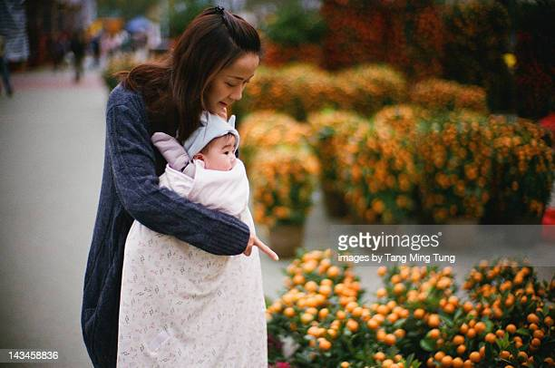 Mother carrying child in flower market