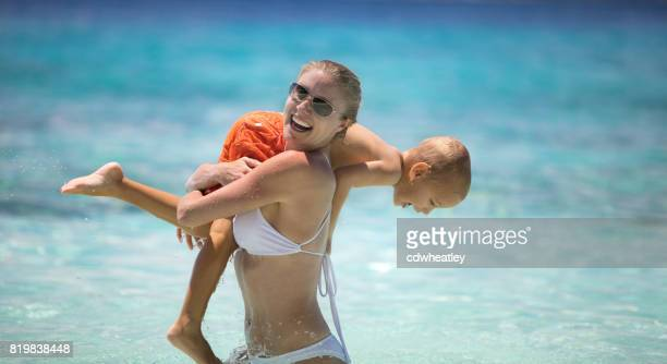 mother carrying child on her shoulder at a tropical beach in the Caribbean
