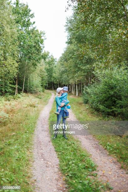 mother carrying child while hiking in forest - chest kissing stock pictures, royalty-free photos & images