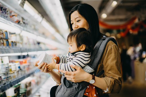 Mother carrying cute baby girl grocery shopping in supermarket and reading nutrition label on the package of fresh yoghurt - gettyimageskorea