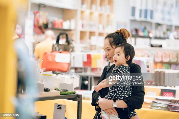 Mother Carrying Cute Daughter At Supermarket