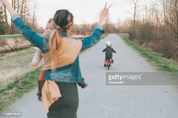 mother carrying daughter and cheering her little son, riding bicycle - loslassen aktivitäten und sport stock-fotos und bilder