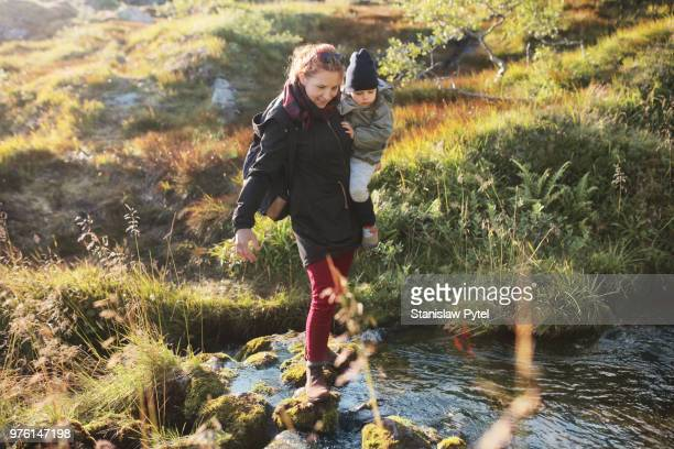 Mother carrying daughter, crossing river in mountains