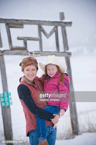 Mother carrying daughter (4-5) in snow, smiling