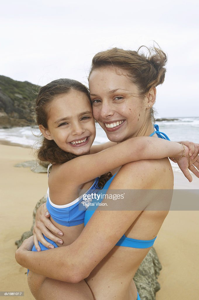 Mother Carrying Daughter on a Beach : Stock Photo