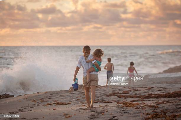 mother carrying daughter on beach at sunrise, blowing rocks preserve, jupiter island, florida, usa - jupiter island florida stock photos and pictures