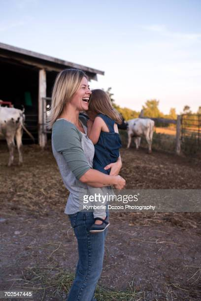 Mother carrying daughter on farm, mother laughing