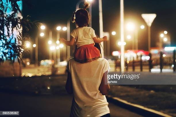 Mother carrying daughter on shoulders at night New York city