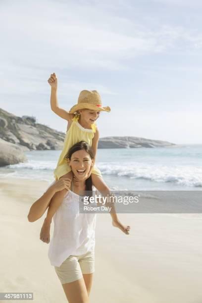 Mutter tragen Tochter auf Schultern am Strand