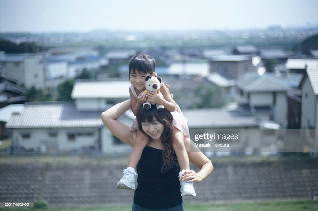 Mother carrying daughter (3-5) on shoulders, smiling : Stock Photo