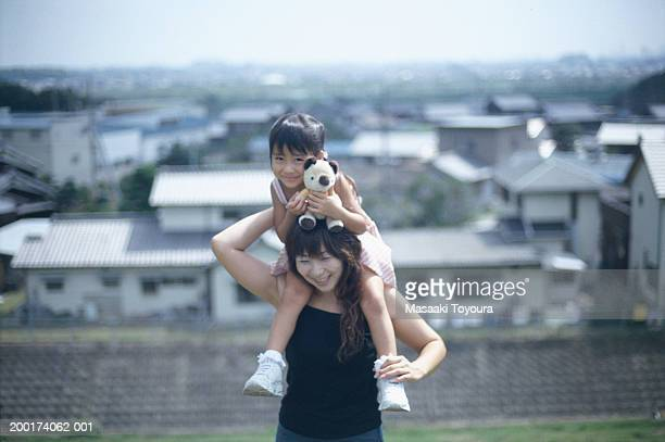 mother carrying daughter (3-5) on shoulders, smiling - region kinki stock-fotos und bilder