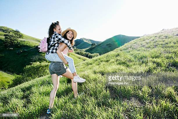 mother carrying daughter piggyback on hill - green shorts stock photos and pictures