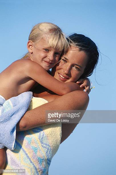mother carrying daughter (4-5), smiling, portrait - mother daughter towel stock photos and pictures