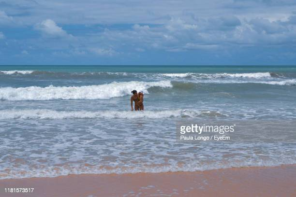 mother carrying daughter while standing in sea against sky - natal brazil stock pictures, royalty-free photos & images