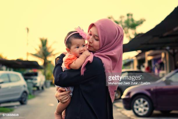 mother carrying daughter while standing on road - muslim mother stock pictures, royalty-free photos & images