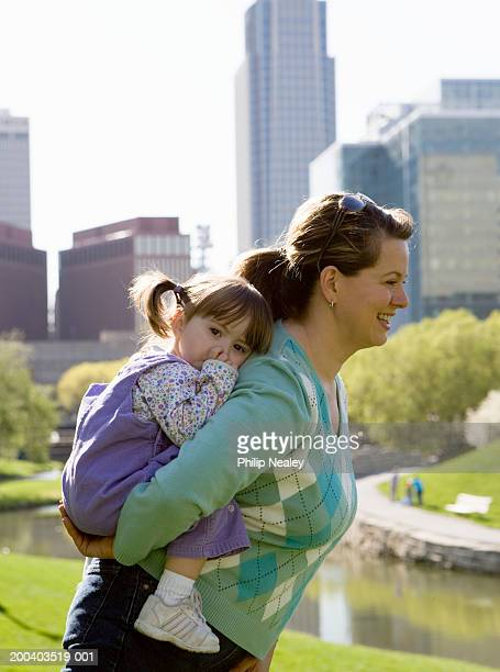 Mother carrying girl (21-24 months) on back in park, side view