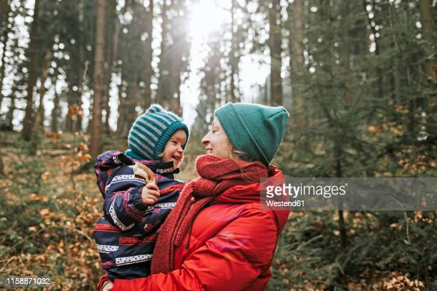 mother carrying happy little daughter in autumnal forest - red coat stock pictures, royalty-free photos & images