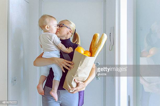 Mother carrying her baby and a grocery bag