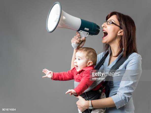 mother carrying her baby and shouting through megaphone - announcement message stock pictures, royalty-free photos & images