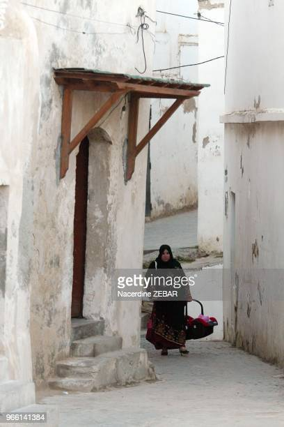 Mother carrying her baby in Kasbah streets of Algiers on May 23 2012 in Algiers Algeria