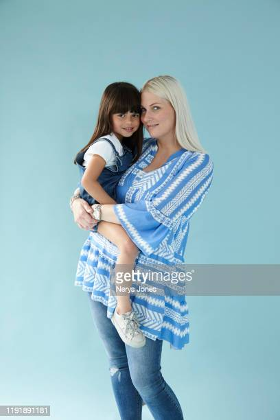 mother carrying her child against pale blue background - nerys jones stock photos and pictures
