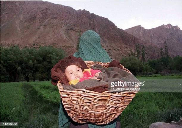 Mother carrying her child flees from her village, Minji, near Kargil, 26 May 1999, where shelling has disrupted normal life. Waves of Indian jets...