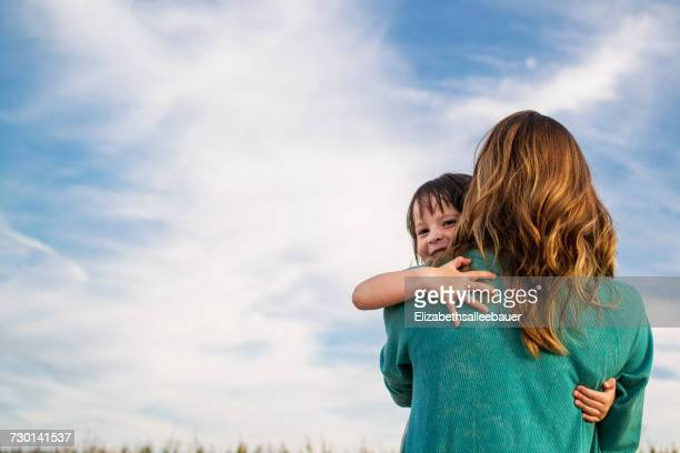 mother carrying her daughter on her shoulder - passer le bras autour photos et images de collection