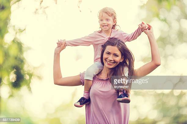 Mother carrying her little girl on shoulders.