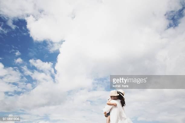 Mother carrying her son under blue sky