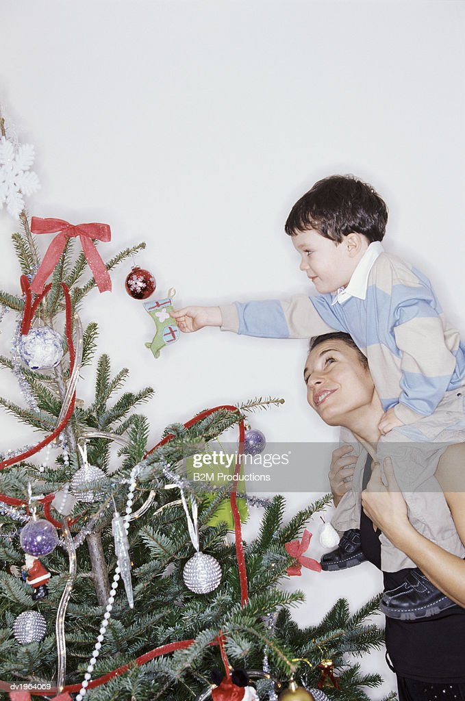Mother Carrying Hr Son on Her Shoulders, Boy Decorating a Christmas Tree : Stock Photo