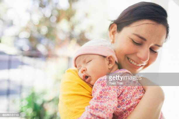 mother carrying sleeping baby girl - human fertility stock pictures, royalty-free photos & images