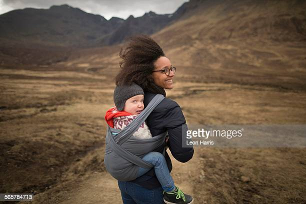 Mother carrying son in sling, Fairy Pools, near Glenbrittle, Isle of Skye, Hebrides, Scotland