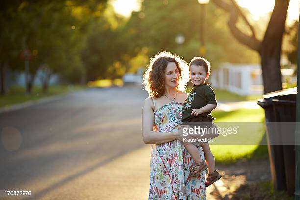 Mother carrying son in the sunset