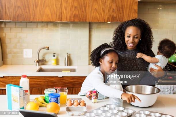 mother carrying son looking at daughter making cupcakes in kitchen - milk carton stock photos and pictures