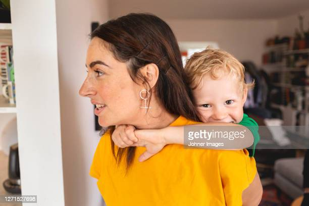 mother carrying son on back - piggyback stock pictures, royalty-free photos & images