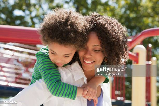 Mother carrying son on playground
