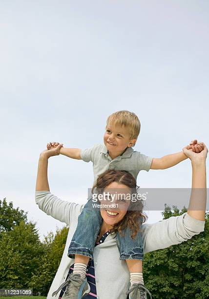 Mother carrying son on shoulders, smiling
