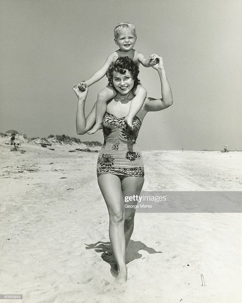 Mother carrying son (2-3) on shoulders, walking on beach, (B&W), portrait : Stock Photo
