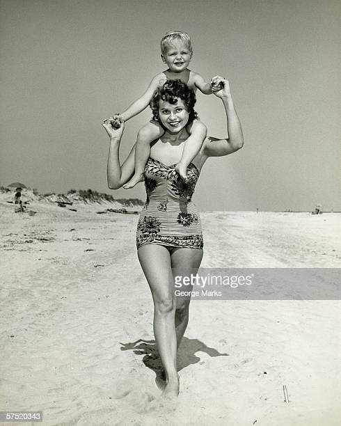 mother carrying son (2-3) on shoulders, walking on beach, (b&w), portrait - swimwear photos stock photos and pictures