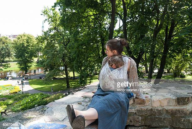 Mother Carrying Son While Sitting On Wall At Park