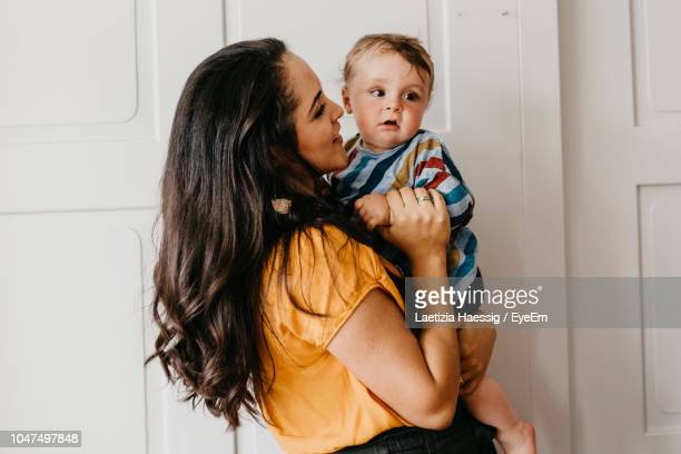 mother carrying son while standing by door at home - babyhood stock pictures, royalty-free photos & images