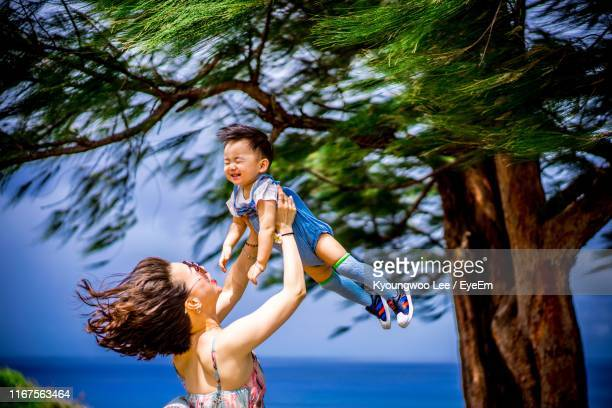 mother carrying son while standing by tree against sky - guam stock pictures, royalty-free photos & images