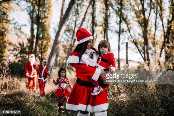 mother carrying toddler baby while dressed as santa claus in forest - mamma natale foto e immagini stock