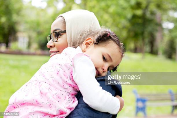 Mother carrying young child in public park