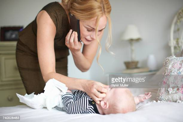 mother changing baby sons nappy while using mobile phone - bent over babes stock pictures, royalty-free photos & images