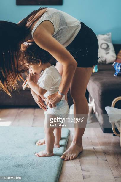 mother changing diaper on toddler while standing - diaper kids stock pictures, royalty-free photos & images